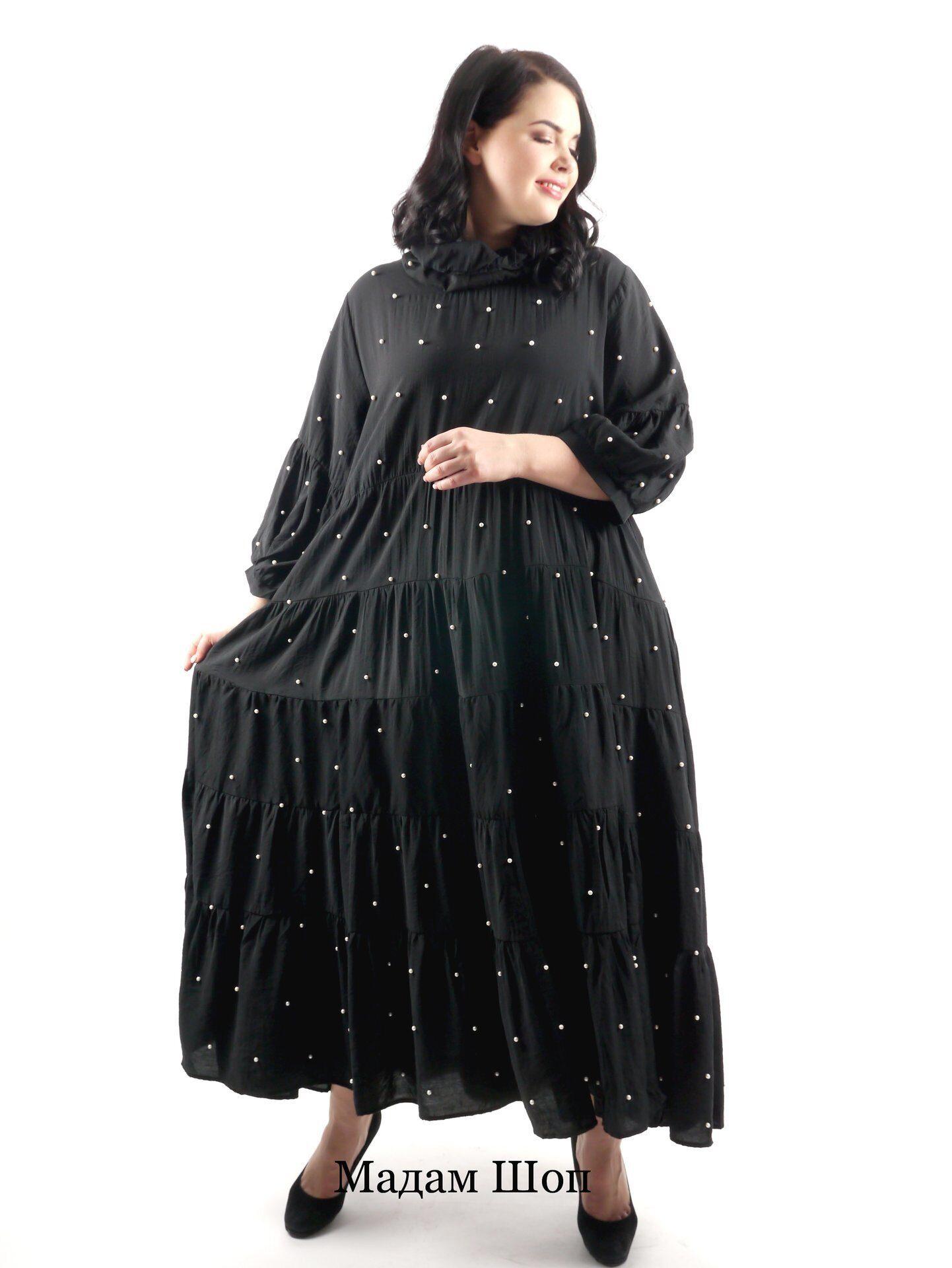 e866c490c42 Многоярусное черное свободное платье украшено искусственным жемчугом.  Женственность строгому образу придают длинные рукава-фонарики