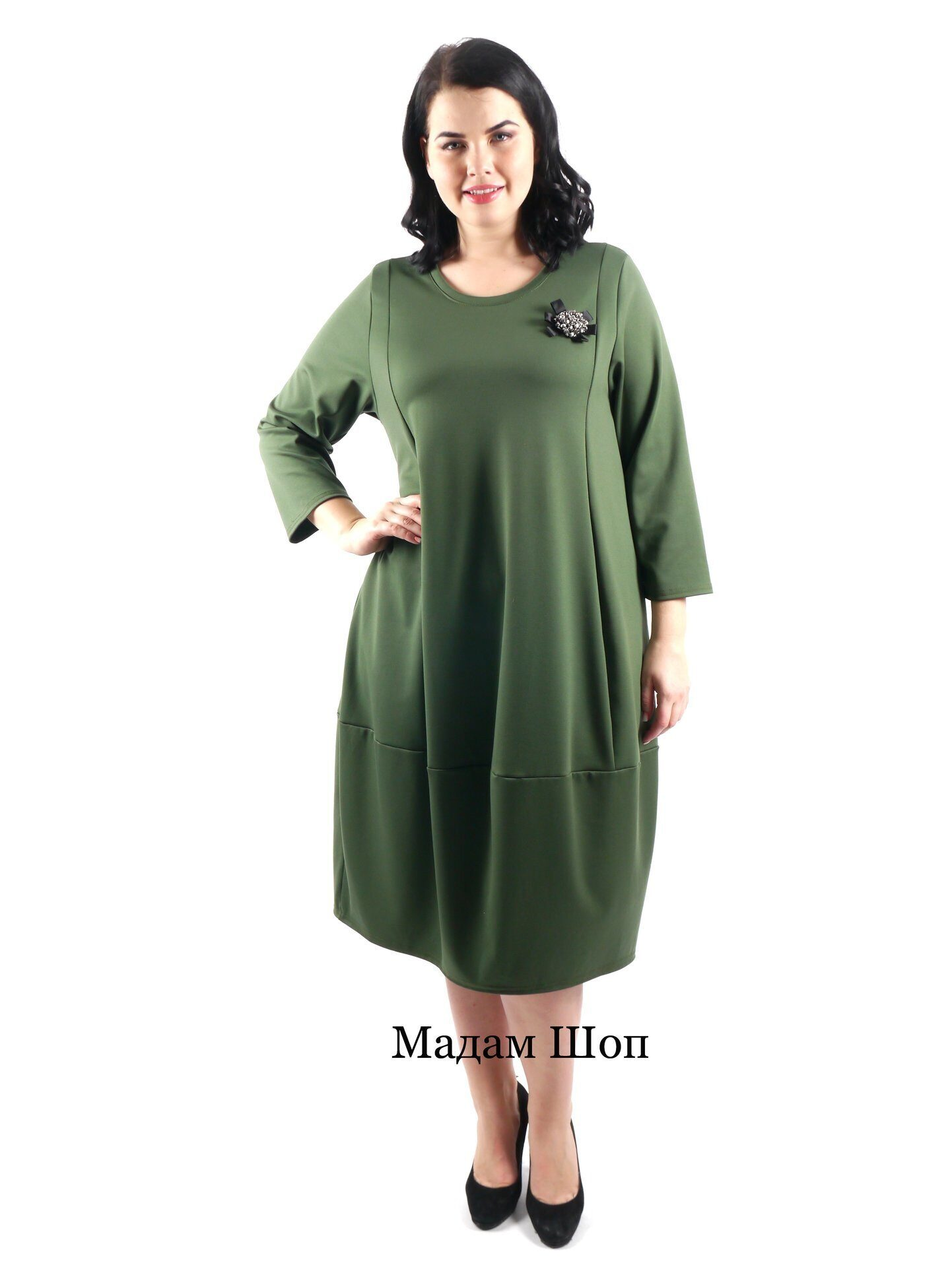 ee082702fdc Стильное зеленое платье с рукавом 3 4 украшено большой брошью из ограненных  бусин и бисера